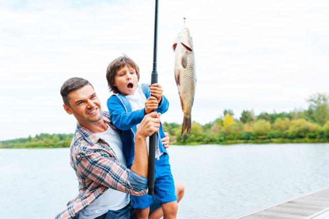 It is so big! Father and son stretching a fishing rod with fish on the hook